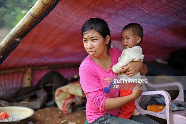 This picture taken on April 6 2015 shows a Kokang refugee holding her child at a temporary shelter in the border area of China and Myanmar in Nansan...