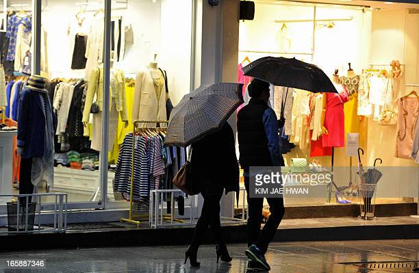 This picture taken on April 6 shows pedestrians in the shopping district of Gangnam in the South Korean capital Seoul where businesses have remained...