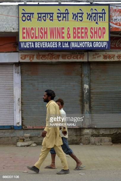 This picture taken on April 7 2017 shows people walking past a closed liquor shop near a national highway on the outskirts in Amritsar Thousands of...