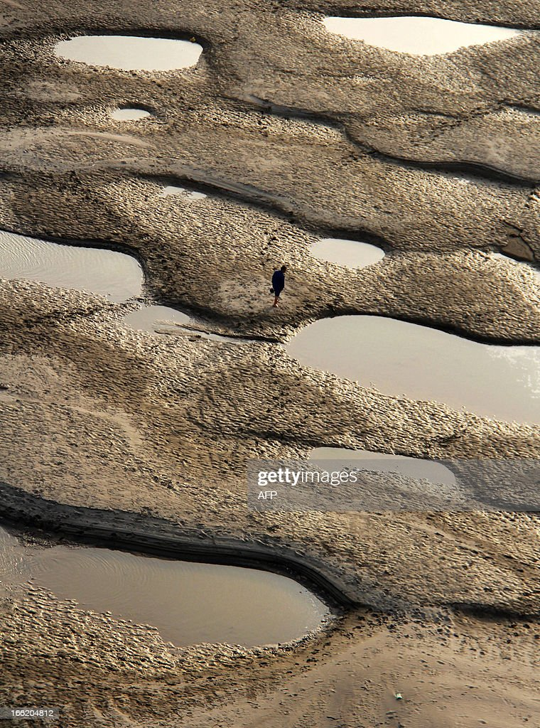 This picture taken on April 9, 2013 shows a man walking along the riverbed of the Hanjiang River during its dry season in Shiyan, central China's Hubei province. China's coastal waters are suffering 'acute' pollution, with the size of the worst affected areas soaring by more than 50 percent last year, an official body said. CHINA
