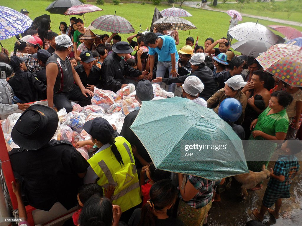 This picture taken on August 1, 2013 shows flood victims receiving food relief from volonteers at a relief camp in Myawaddy. Tens of thousands of people were sheltering in relief camps in eastern Myanmar after flash floods swept the region leaving three dead, state media said, warning of more heavy rain to come.