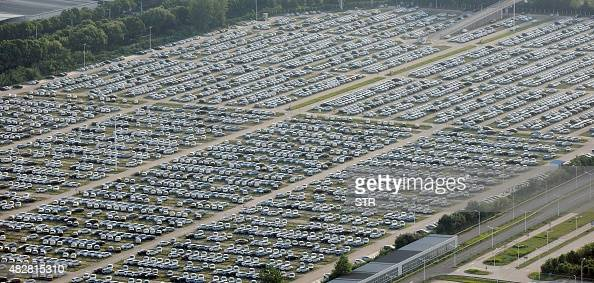 This picture taken on August 1 2015 shows newlymanufactured cars at a parking area in the Wuhan developent zone central China's Hubei province A key...