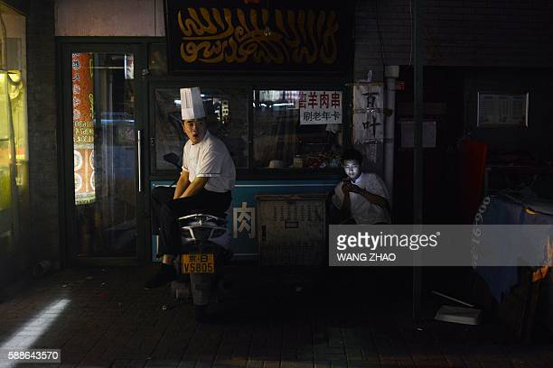 TOPSHOT This picture taken on August 11 2016 shows two cooks having a rest outside a butcher shop in Beijing / AFP / WANG ZHAO
