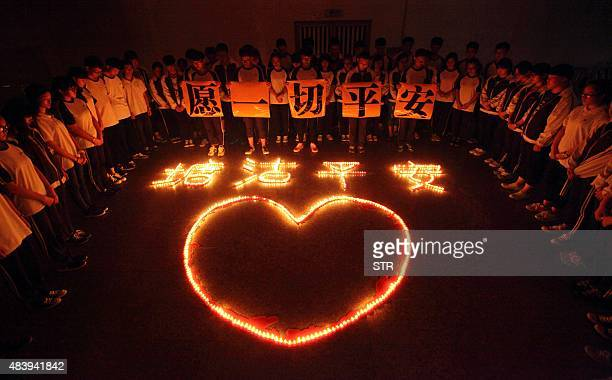 This picture taken on August 13 2015 shows students at Hailiang International School lighting at a vigil to pray for the victims of the explosions at...
