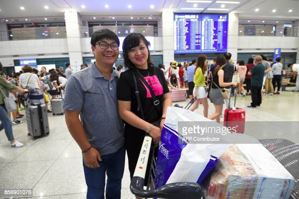 This picture taken on August 14 2017 shows Vietnamese bride Huynh Thi Thai Muoi and her South Korean husband Kim KyeongBok after their arrival at...