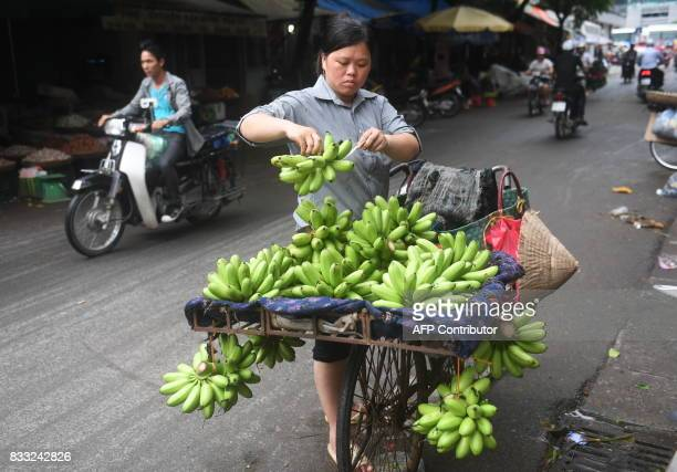 TOPSHOT This picture taken on August 16 2017 shows a fruit vendor selling green bananas in the old quarter of Hanoi / AFP PHOTO / HOANG DINH NAM