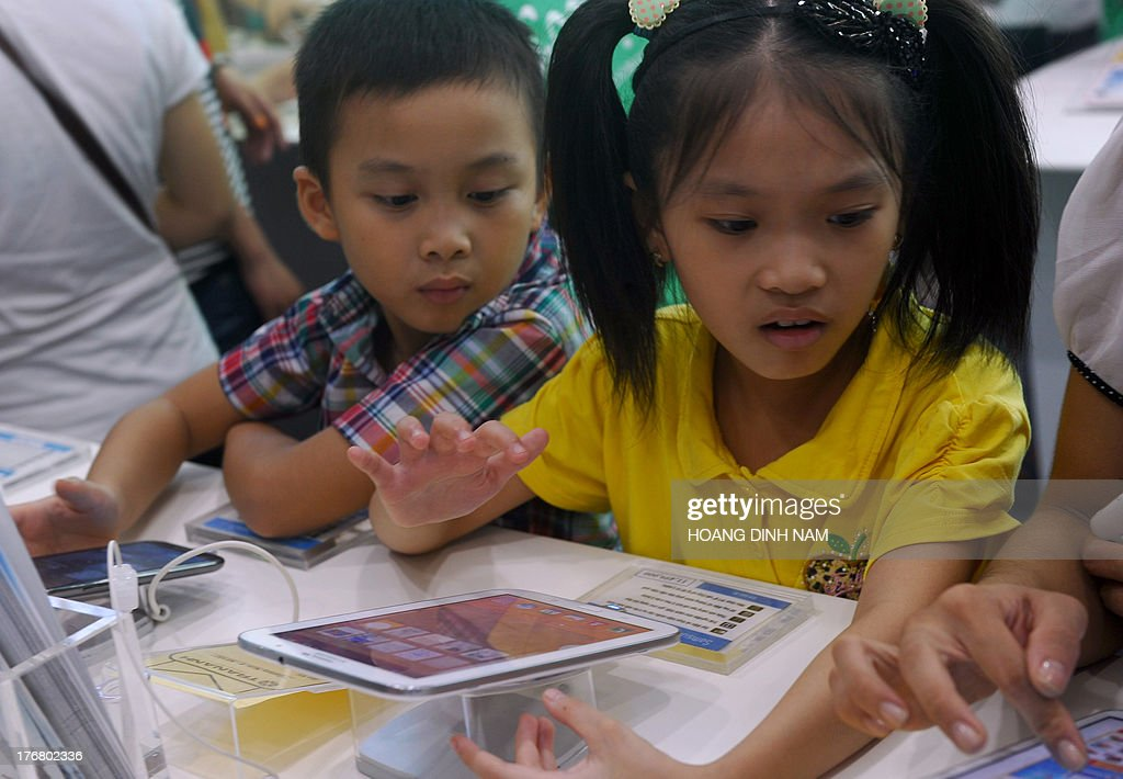 This picture taken on August 17, 2013 shows children looking at laptops and tablets at a computer shop at a newly opened mall in Hanoi. IT products and especially new mobile products like smartphone and tablets have had a great impact on the communist nation's young people . AFP PHOTO/HOANG DINH Nam