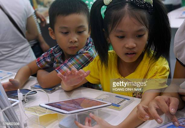 This picture taken on August 17 2013 shows children looking at laptops and tablets at a computer shop at a newly opened mall in Hanoi IT products and...