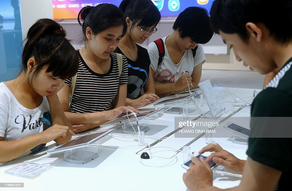This picture taken on August 17, 2013 shows people inspecting smartphones and tablets at a computer shop at a newly opened mall in Hanoi. IT products and especially new mobile products like smartphone and tablets have had a great impact on the communist nation's young people . AFP PHOTO/HOANG DINH Nam