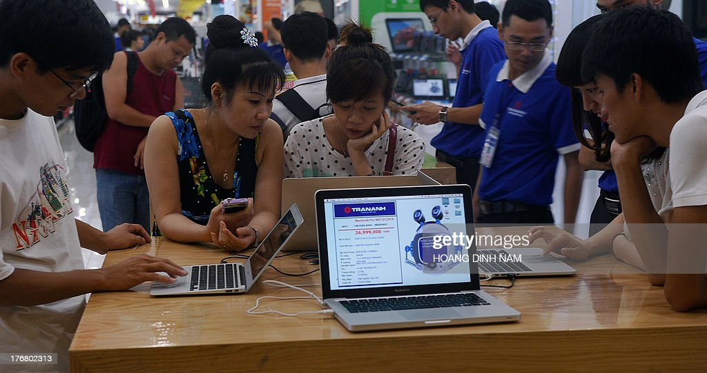 This picture taken on August 17, 2013 shows people inspecting laptops and tablets at a computer shop at a newly opened mall in Hanoi. IT products and especially new mobile products like smartphone and tablets have had a great impact on the communist nation's young people . AFP PHOTO/HOANG DINH Nam