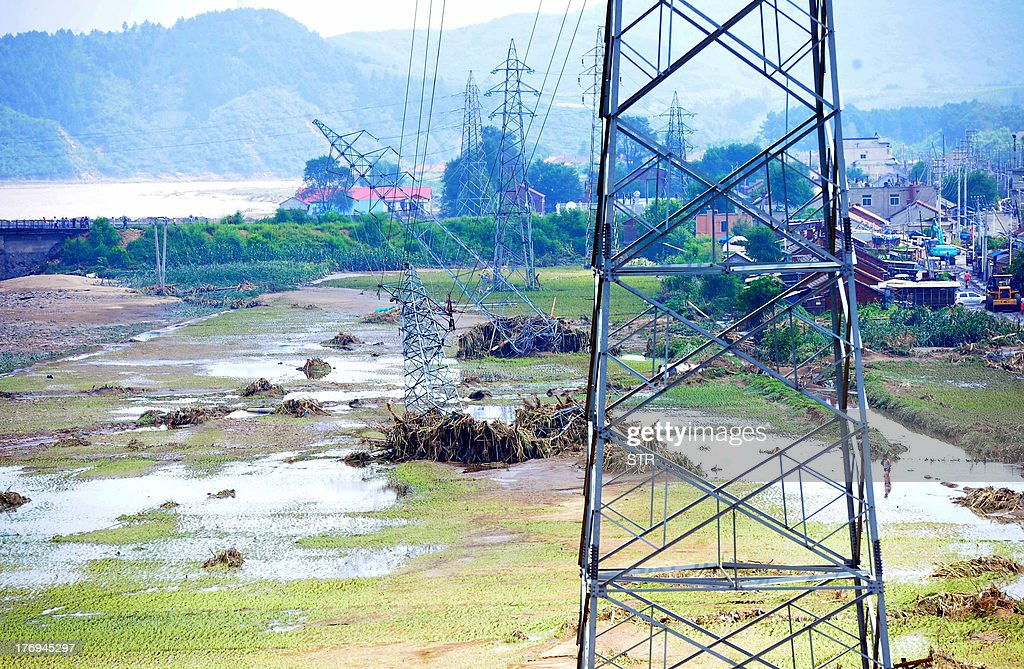 This picture taken on August 18, 2013 shows damaged power transmission towers (C) leaning to the ground after being damaged by floods in the Qingyuan Manchu autonomous county of Fushun, in northeast China's Liaoning province. Devastating floods at opposite ends of China have left 105 people dead and another 115 missing in recent days, state media said on August 19. Flooding in the northeast which left 72 people dead was described as 'the worst in decades' by the state news agency, while another 33 people died in the south as a result of the weather, it said citing the ministry of civil affairs. CHINA