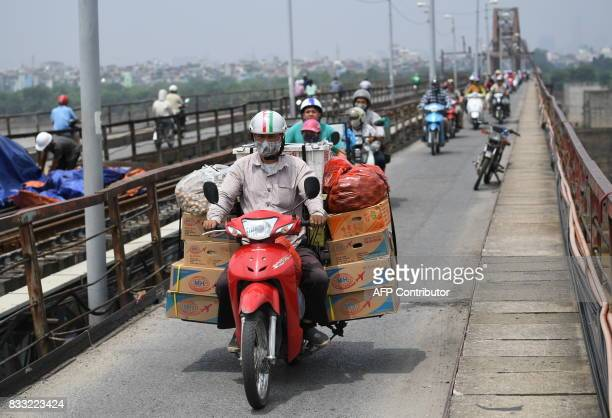 This picture taken on August 2 2017 shows a man transporting goods on his motorcycle as he crosses Long Bien bridge over the Red River in Hanoi / AFP...