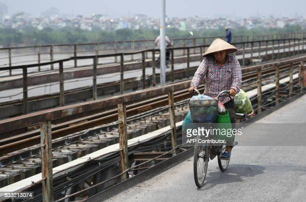 This picture taken on August 2 2017 shows a vendor transporting goods on her bicycle as she crosses Long Bien bridge over the Red River in Hanoi /...