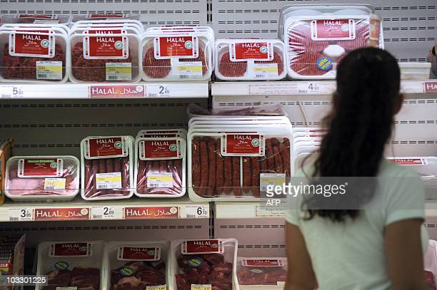 This picture taken on August 21 2009 in Illzach eastern France shows a customer passing by Halal butchery shelves in a supermarket on the eve of the...