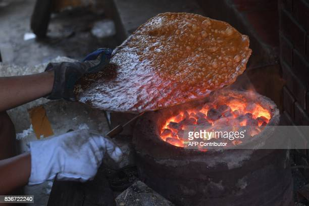 This picture taken on August 21 2017 shows a villager grilling rice crackers at his home in Tho Ha village northern province of Bac Giang / AFP PHOTO...