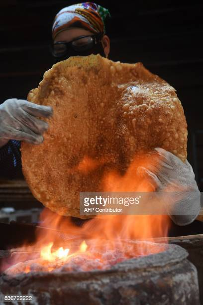 This picture taken on August 21 2017 shows a woman grilling rice crackers at her home in Tho Ha village northern province of Bac Giang / AFP PHOTO /...