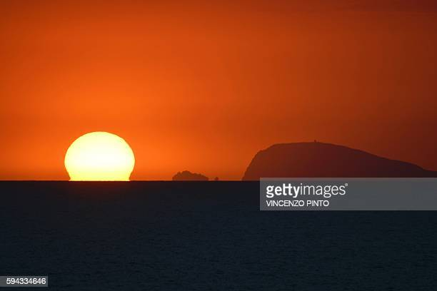 This picture taken on August 22 2016 shows the sun setting down behind the sea on the Italian island of Ventotene / AFP / VINCENZO PINTO