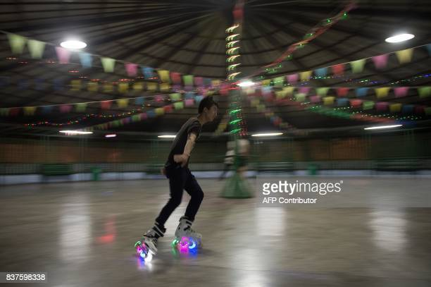 This picture taken on August 22 2017 shows a man rollerblading at a roller disco inside a park in Harbin / AFP PHOTO / NICOLAS ASFOURI