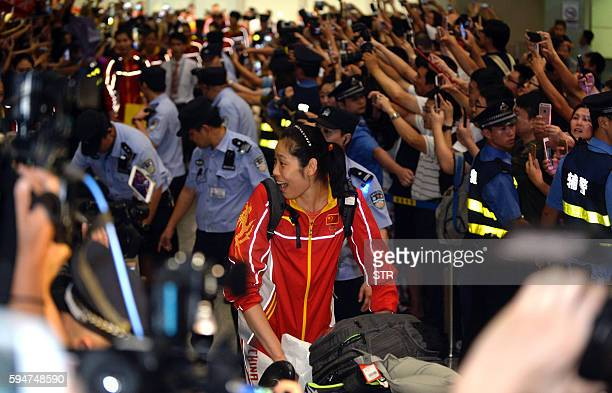 This picture taken on August 23 2016 shows players of the Chinese national women volleyball team being welcomed home by fans as they arrive at...