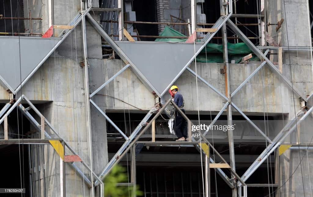 This picture taken on August 27, 2013 shows a laborer working on scaffolding outside the Wanda Reign Wuhan Hotel, which is still under construction in Wuhan, central China's Hubei province. China's leaders will gather in November for a key meeting on economic reforms, state media said on August 28, the third time they will have met since a generational handover of power last year. CHINA