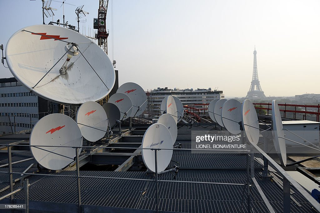 This picture taken on August 28, 2013 on the roof of the Maison de la Radio in Paris, shows antennas and satellite dishes, in front of the Eiffel tower (background).