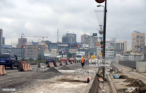 This picture taken on August 28 2015 shows workers carrying out road improvement works on the General DeGaulle Bridge in Abidjan AFP PHOTO / ISSOUF...