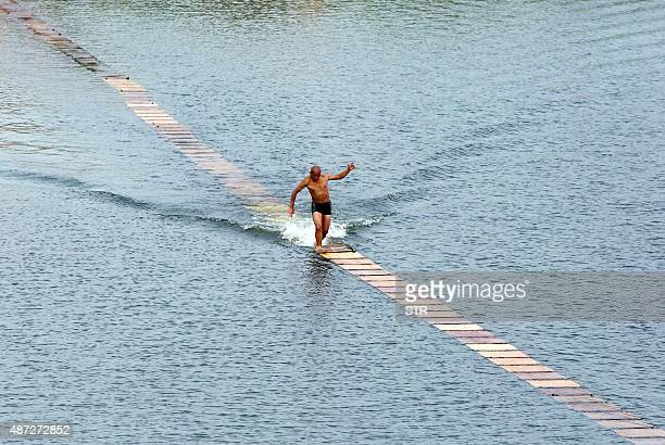 This picture taken on August 29 2015 shows a Shaolin monk breaking his own world record for 'running on water' in Quanzhou Fujian province Shi...
