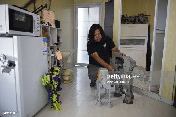 This picture taken on August 29 2017 shows Sun Shiqian a Chinese artist who makes transformerlike sculptures checking a robot dog at his studio in...