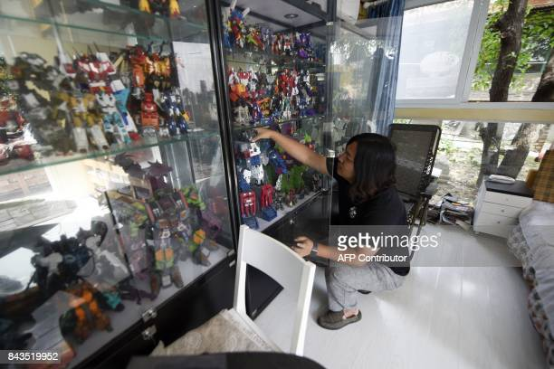 This picture taken on August 29 2017 shows Sun Shiqian a Chinese artist who make transformerlike sculptures checking his collected transformers at...
