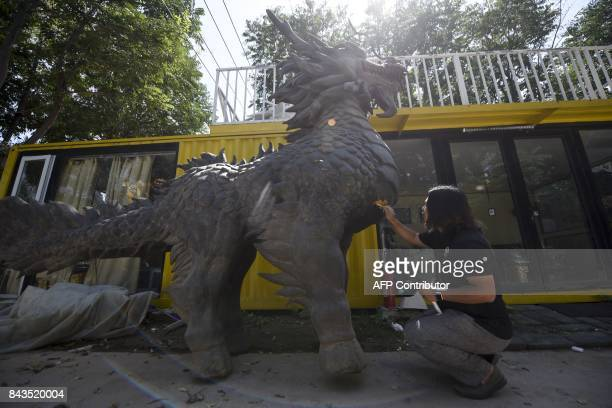 This picture taken on August 29 2017 shows Sun Shiqian a Chinese artist who makes transformerlike sculptures reparing a dragon sculpture at his...