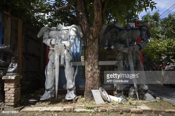 This picture taken on August 29 2017 shows two transformerlike sculptures designed by Sun Shiqian at his studio in Beijing Sun Shiqian's roomy...