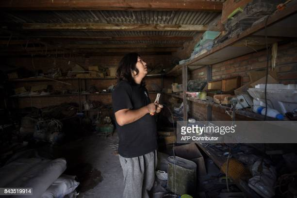 This picture taken on August 292017 shows Sun Shiqiana Chinese artist who makes transformerlike sculptures checking his tools at his studio in...