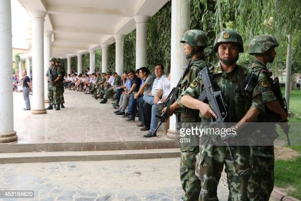 This picture taken on August 3 2014 shows soldiers keeping watch as residents attend the awarding ceremony for those who helped in the killing and...
