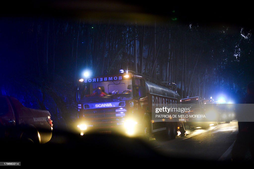 This picture taken on August 30, 2013 shows firefighting vehicles on a road after a wildfire in Caramulo, central Portugal. Firefighters battled wildfires on August 30 in Portugal where they have claimed five lives and tamed another major blaze in northern Spain, officials said. In Portugal, some 1,400 firefighters backed by Spanish and French aircraft were battling a series of fires that have ravaged thousands of hectares of forest in the north and centre of the country.