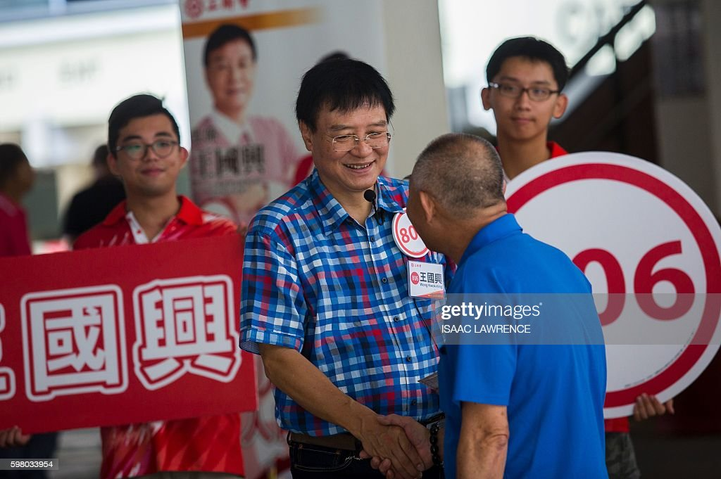 This picture taken on August 30 2016 shows proBeijing candidate Wong Kwokhing from the political party Hong Kong Federation of Trade Unions shaking...