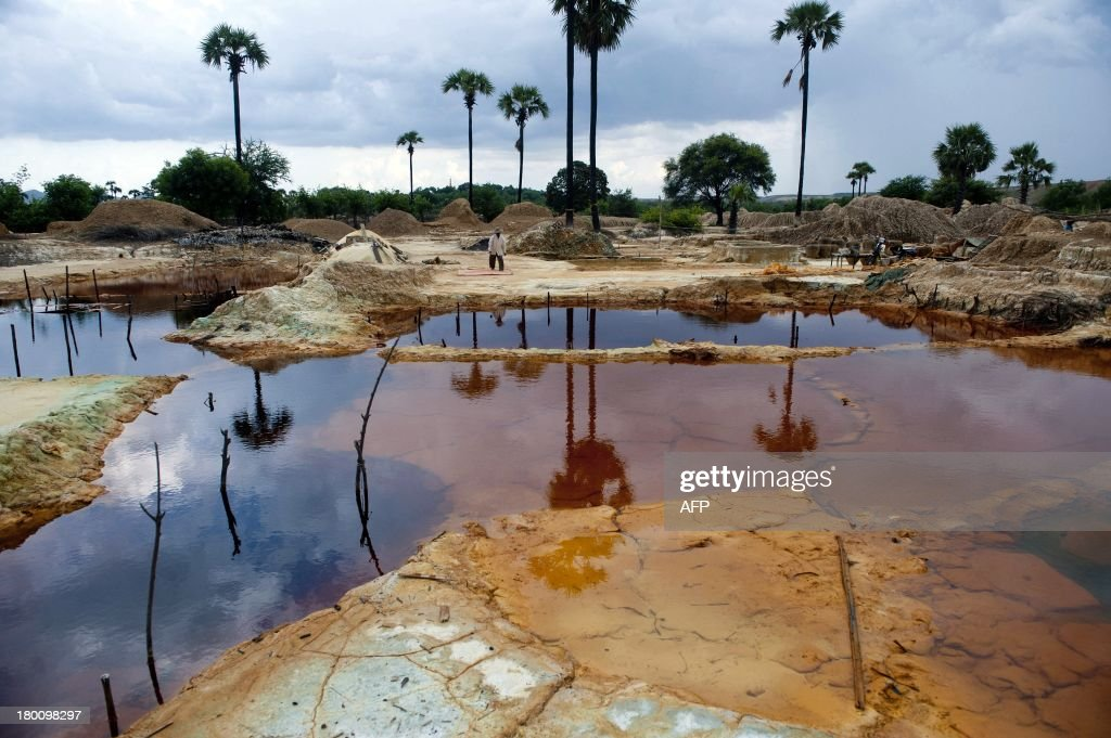 This picture taken on August 31 2013 shows a worker walking by pools in a mining waste dump area in Monywa northwestern Myanmar Villagers whose lands...