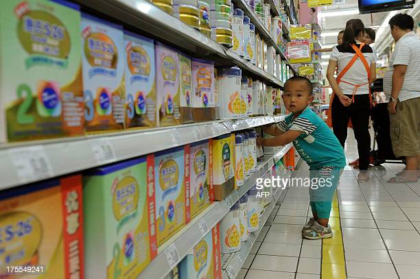 This picture taken on August 4 2013 shows a baby playing in the imported baby products section while his parents purchase baby products of a...