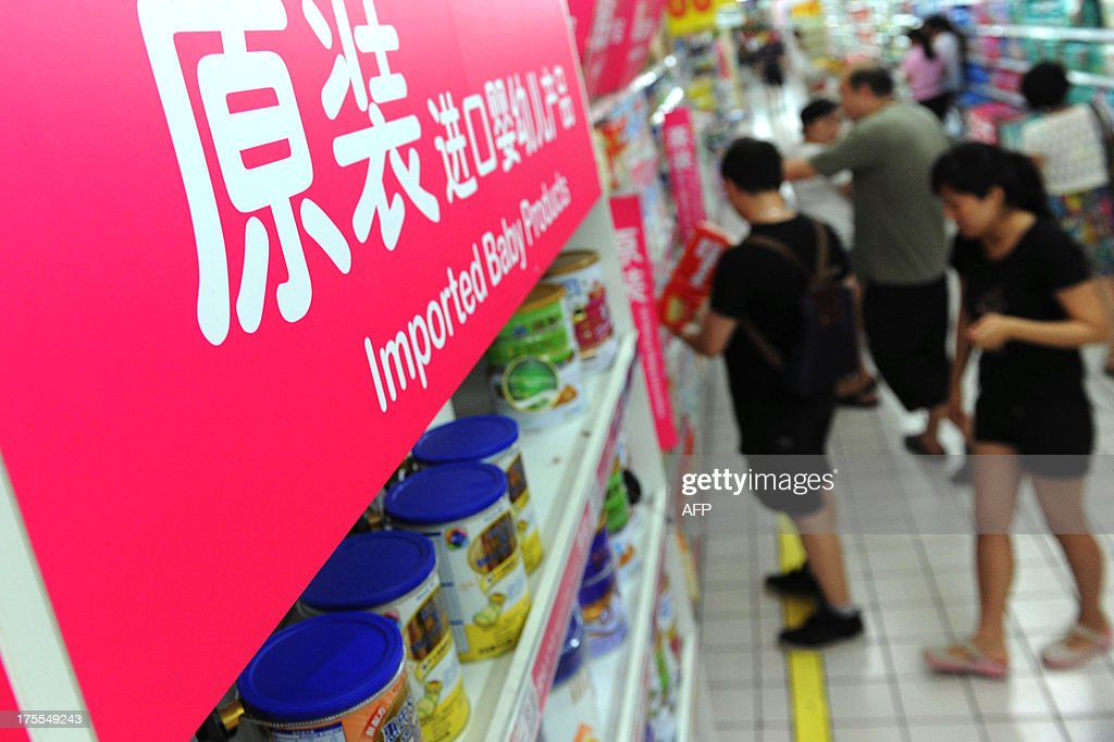 This picture taken on August 4, 2013 shows customers shopping in the imported baby products section while his parents purchase baby products of a supermarket in Beijing. New Zealand warned international health authorities on August 3 of exported dairy products, including infant formula, containing a bacteria that could lead to botulism -- a potentially fatal illness. CHINA