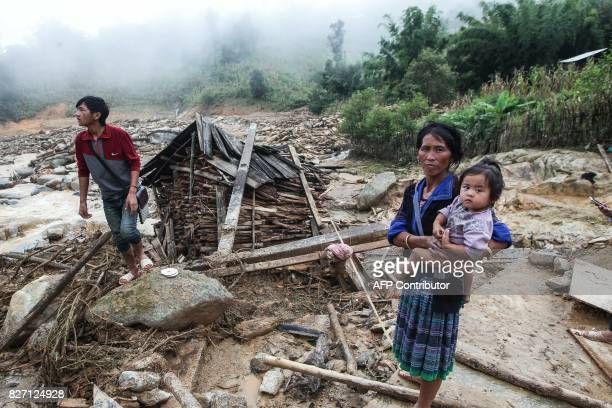 This picture taken on August 4 2017 shows Hmong hilltribe villagers walking amid homes destroyed by flash floods in the mountainous district of Mu...