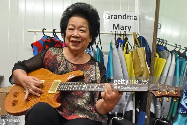 This picture taken on August 5 2017 shows Mary Ho also known as Grandma Mary posing with her electric guitar during a rehearsal in Singapore An...