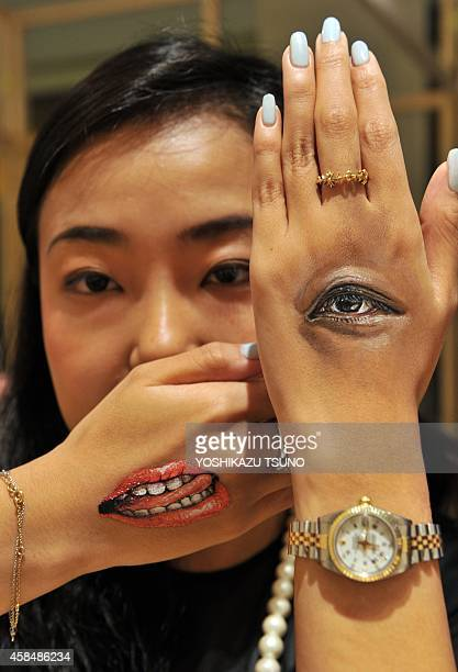 This picture taken on August 6 2014 shows a body painting of an eye and mouth on the back of Eri Takimoto's hands painted by Japanese bodypainting...