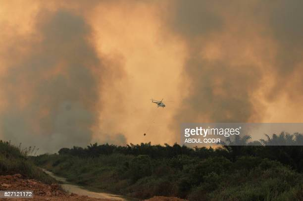 This picture taken on August 6 2017 shows a helicopter operated by the Indonesian Disaster Mitigation Agency conducting water bomb operations to put...