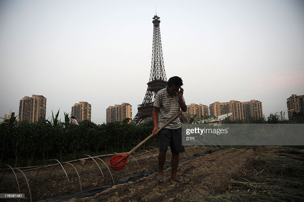 This picture taken on August 7, 2013 shows a resident farming with the background of a replica of the Effel Tower in Tianducheng, a luxury real estate development located in Hangzhou, east China's Zhejiang province. China's ability to reproduce foreign products is best known for imitation luxury purses and copies of Hollywood films. But knockoffs have ranged from a three-dollar version of Kate Middleton's engagement ring to fake Apple stores and an entire Austrian village. CHINA OUT AFP PHOTO
