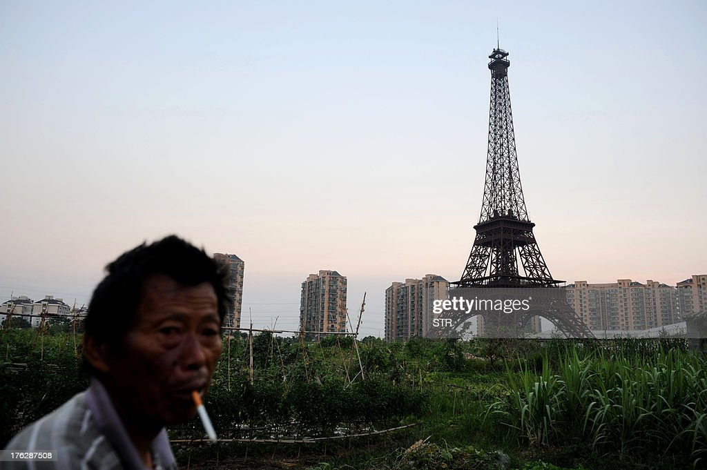 This picture taken on August 7, 2013 shows a resident smoking with the background of a replica of the Effel Tower in Tianducheng, a luxury real estate development located in Hangzhou, east China's Zhejiang province. China's ability to reproduce foreign products is best known for imitation luxury purses and copies of Hollywood films. But knockoffs have ranged from a three-dollar version of Kate Middleton's engagement ring to fake Apple stores and an entire Austrian village. CHINA