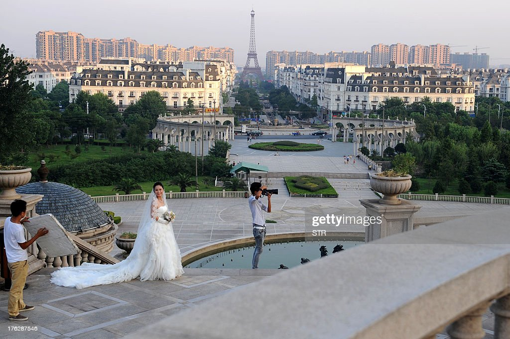 This picture taken on August 7, 2013 shows a woman (2nd L) posing for wedding photos with the background of a replica of the Effel Tower in Tianducheng, a luxury real estate development located in Hangzhou, east China's Zhejiang province. China's ability to reproduce foreign products is best known for imitation luxury purses and copies of Hollywood films. But knockoffs have ranged from a three-dollar version of Kate Middleton's engagement ring to fake Apple stores and an entire Austrian village. CHINA