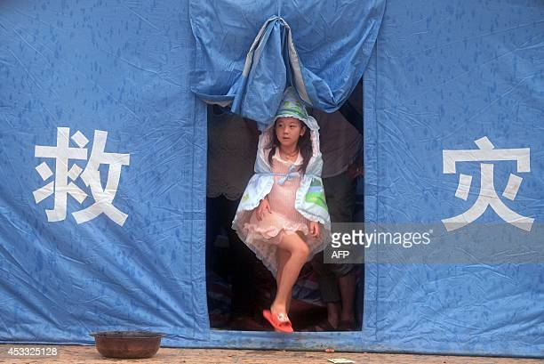 This picture taken on August 7 2014 shows a child leaving a tent as it rains at a temporary shelter in Longtoushan township in Ludian county in...