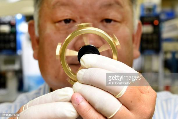 This picture taken on August 7 2017 shows Hiroshi Tsukada employee of Japan's ball bearing maker NSK Micro Precision spinning a fidget spinner after...
