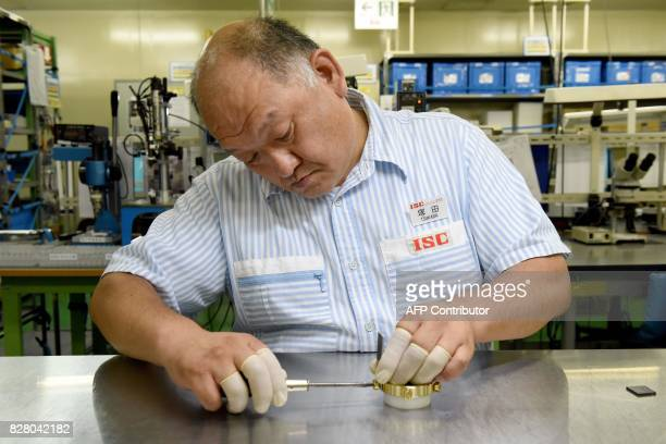 This picture taken on August 7 2017 shows Hiroshi Tsukada employee of Japan's ball bearing maker NSK Micro Precision assembling a fidget spinner at a...