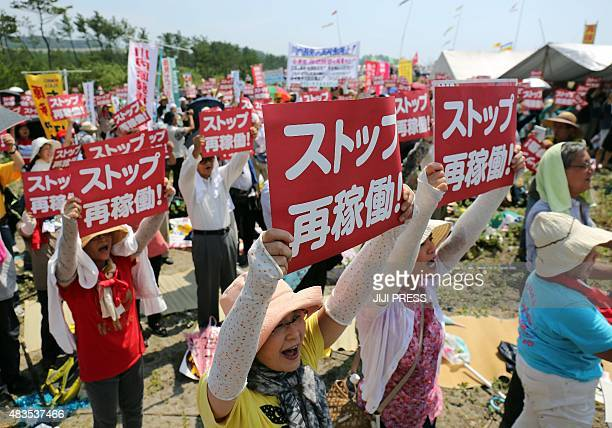 This picture taken on August 9 2015 shows antinuclear protesters holding a rally against the restart of a nuclear reactor in front of the Kyushu...