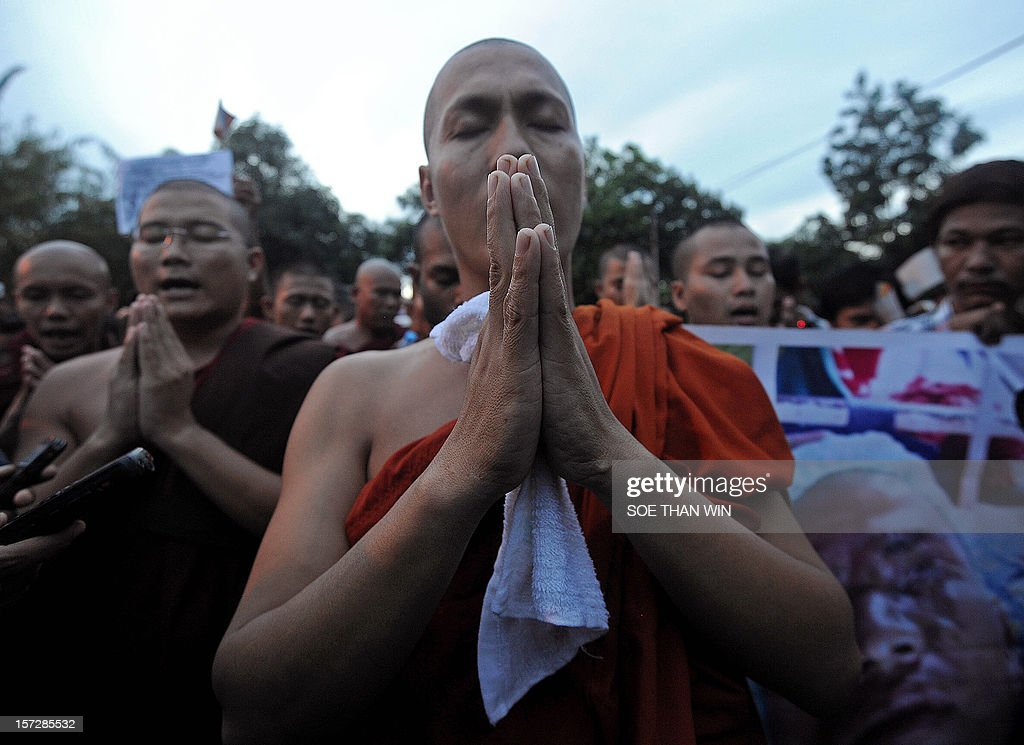 This picture taken on December 1, 2012 shows Buddhist monks praying during a protest near Chinese embassy in Yangon. Police apologised for injuring scores of monks in a crackdown on a protest against a Chinese-backed copper mine on December 29, but tensions over the pre-dawn raid remained high. AFP PHOTO / Soe Than WIN